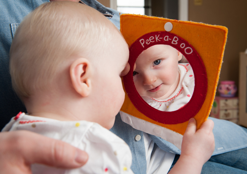 baby looking at its image in a mirror