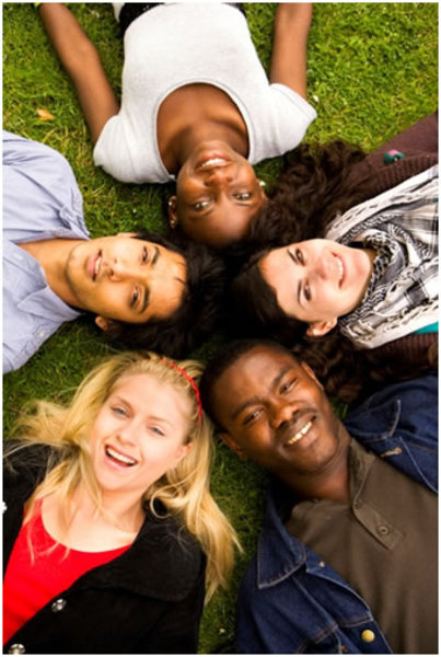 Image depicting diversity with young people lying in a circle on grass